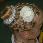 маленькая девочка с волосами собранными в хвост и цветком на голове
