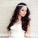 Невеста в красивом белоснежном платье с черными волосами и аксессуаром на голове
