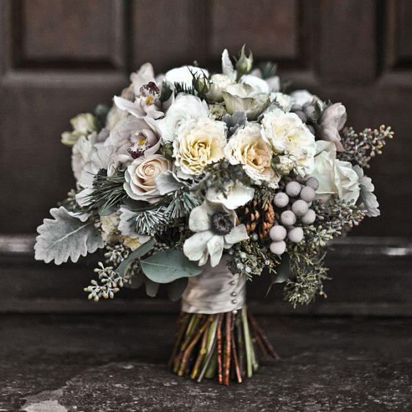 Красивый букет невесты с еловыми ветками и шишками
