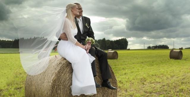 Bride and groom sitting on hay bales